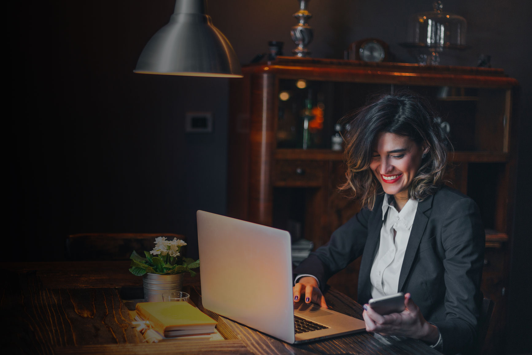 Woman in a darker office working on a laptop, smiling down at her cellphone