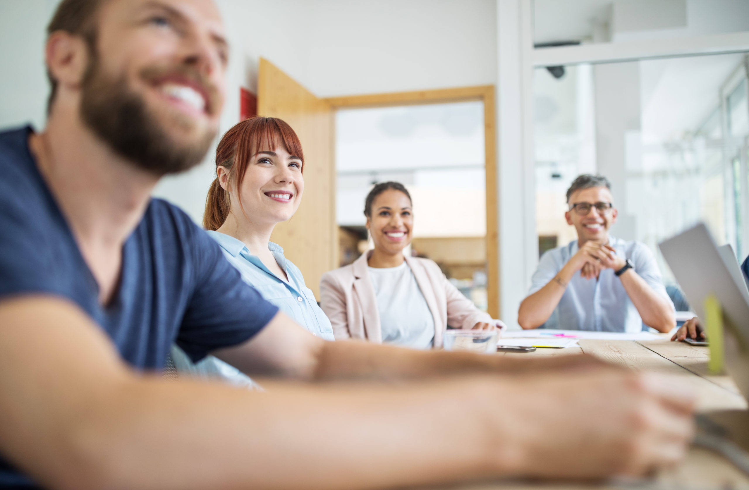 Four employees in an office meeting. They are all smiling and listening to someone talk.