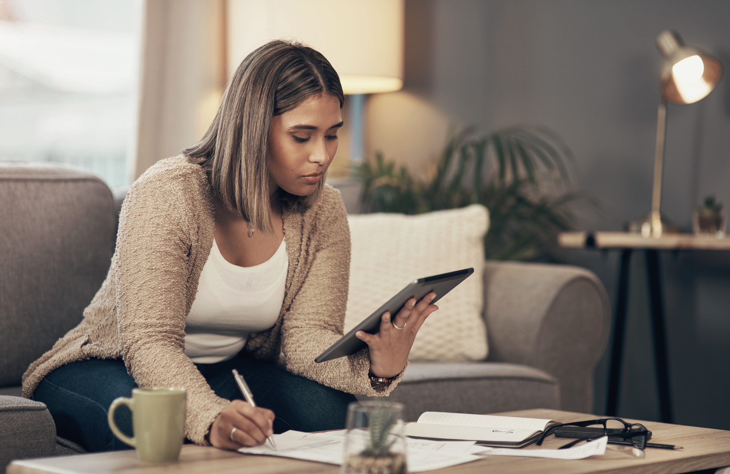 Shot of a young woman using a digital tablet while going through paperwork at home