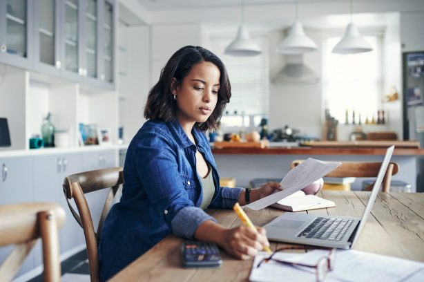 Shot of a young woman using a laptop and going through paperwork while working from home