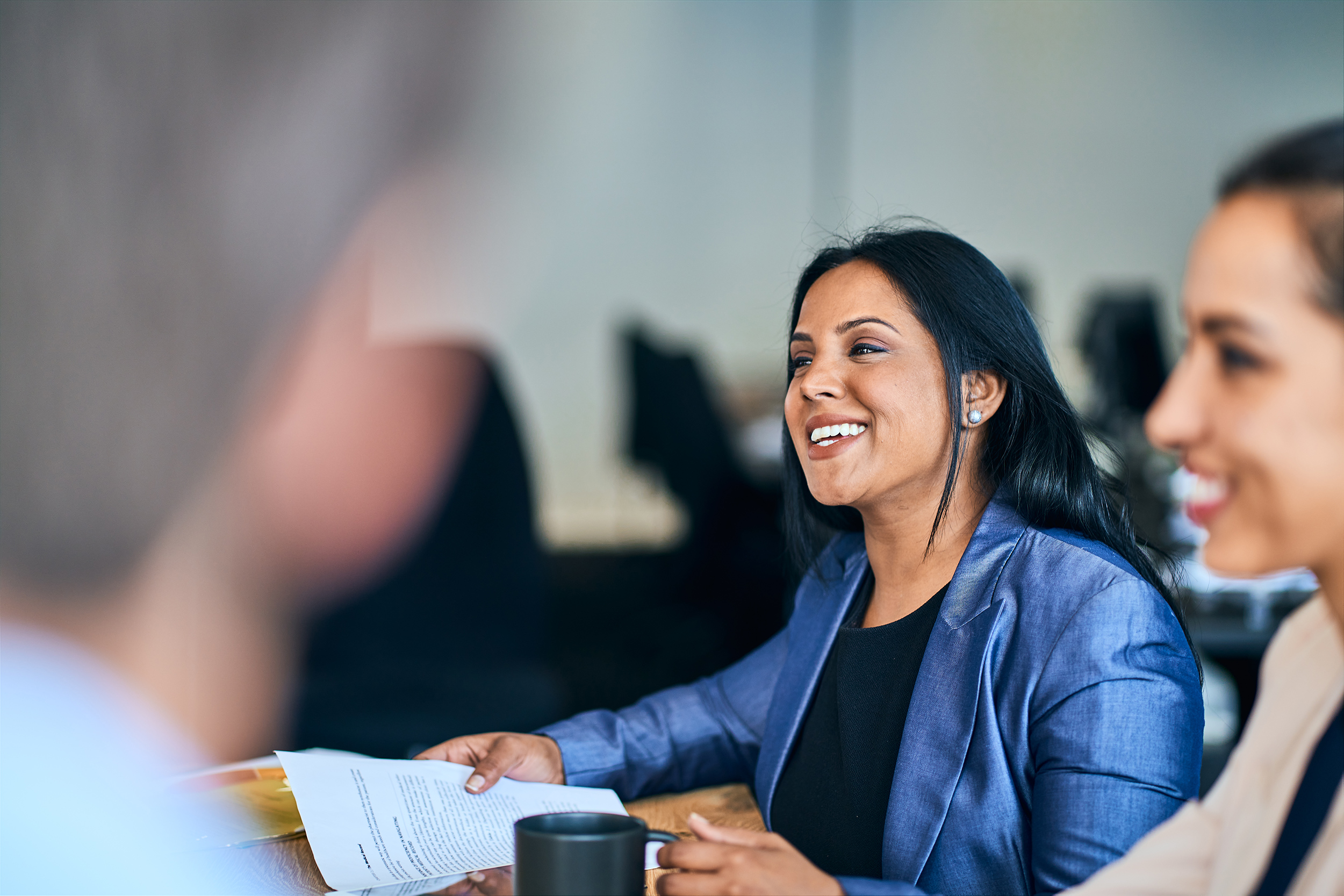 Businesswoman laughing while working with colleagues around a table in a modern open plan office